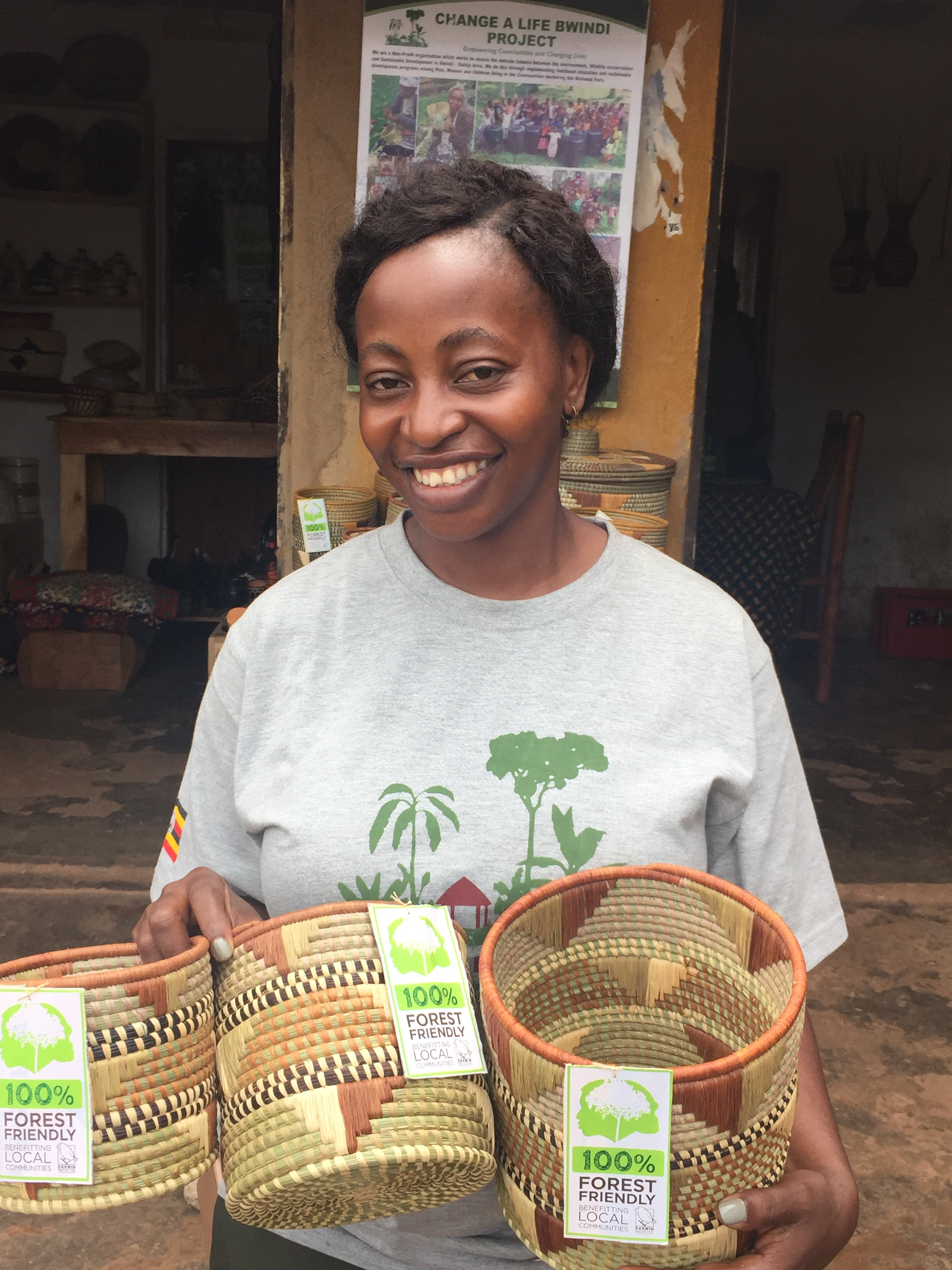 Uganda 23-023 Tina from Change a Life Bwindi, displaying baskets made by women in her cooperative, Credit - Dilys Roe